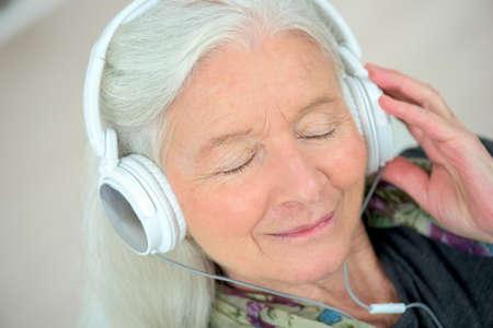 persona de la tercera edad: La señora mayor con los auriculares puestos