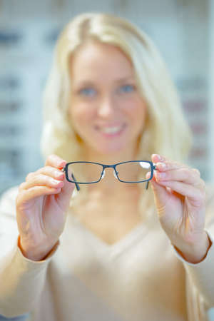 woman shop: Woman trying on a pair of glasses