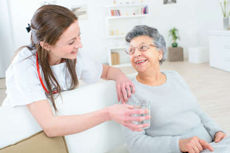 doctor giving glass: Doctor giving old lady a glass of water