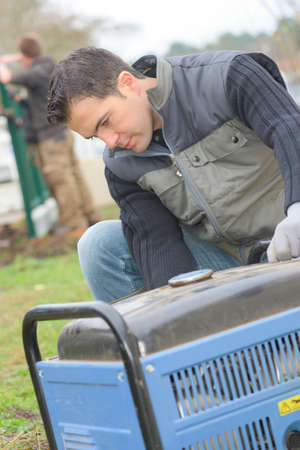 open trench: Builder turning on a mobile generator Stock Photo