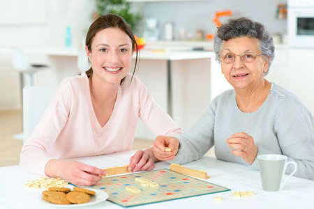 elderly people: Elderly woman playing a board game Stock Photo