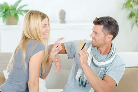 withhold: Couple on sofa, man withholding credit card