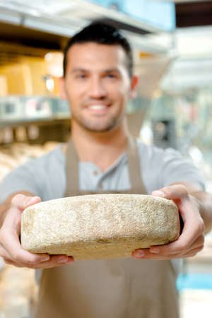 factory farm: Man holding a wheel of cheese