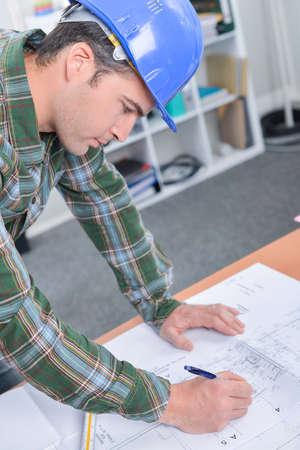 amend: Man amending blueprints