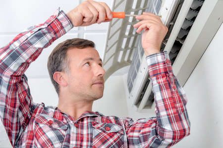 man in air: Man repairing air conditioning unit