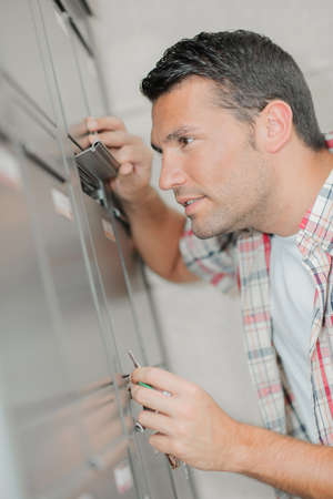 nosey: Man looking through flap of post office box