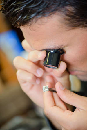 precious metal: Jeweller appraising a ring