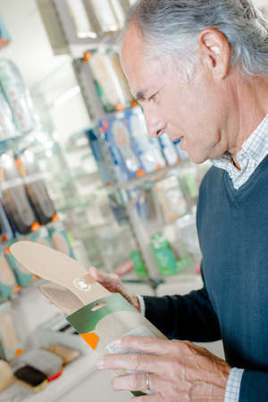out of production: Senior man buying replace soles for his shoes Stock Photo