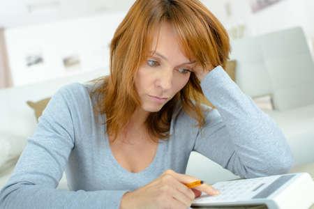 estrés: Señora usando la calculadora, subrayó