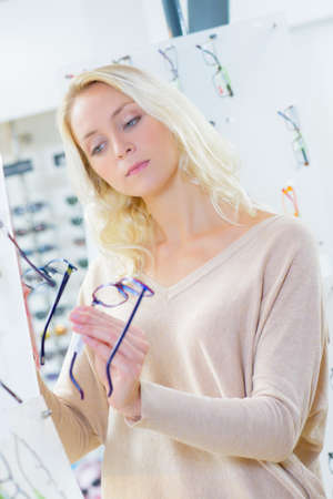 comparing: Lady comparing spectacles Stock Photo