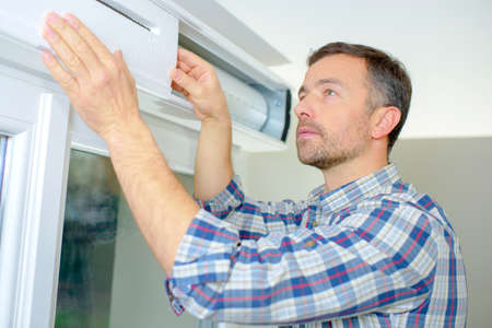 Handyman installing a window shutter Stock Photo - 46954986