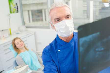 roentgenogram: Male dentist looking at an xray