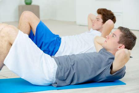 sit ups: Two teenage friends doing sit ups