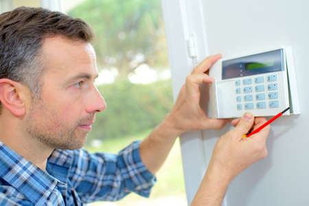 home safety: Electrician fitting an intrusion alarm