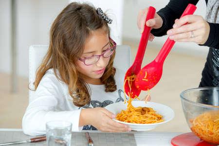 niña comiendo: Niña comiendo espagueti en casa
