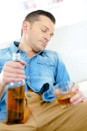 inebriated: Man asleep holding bottle and glass