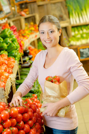 grocers: Lady holding paper bag full of tomatoes Stock Photo