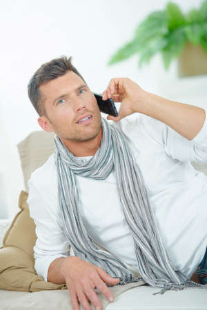 leaning on elbows: Man on couch on telephone Stock Photo