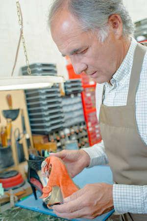 cobbler: cobbler assessing shoe Stock Photo