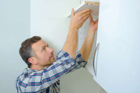 fitter: Worker fitting a kitchen Stock Photo