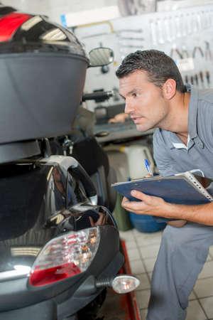 assessing: Mechanic assessing a broken scooter