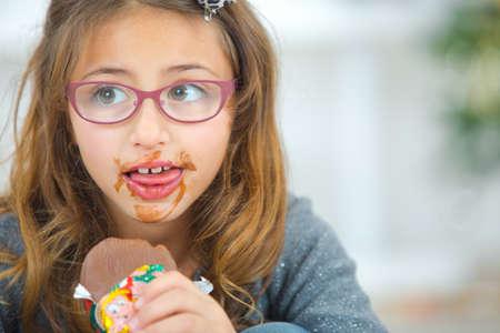 finger food: Greedy little girl eating chocolate Stock Photo