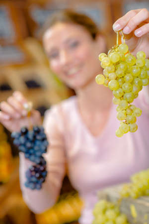 grocers: Woman holding bunches of grapes