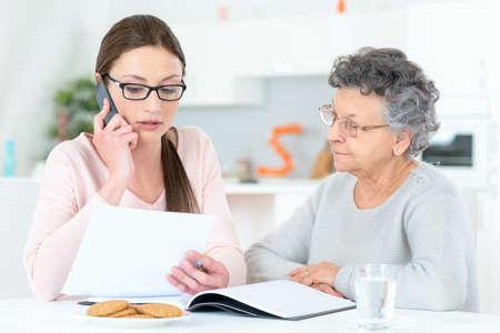 personas ayudando: Ayudar a la señora mayor con sus finanzas