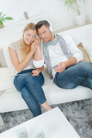 seating furniture: Couple chilling out to music at home Stock Photo