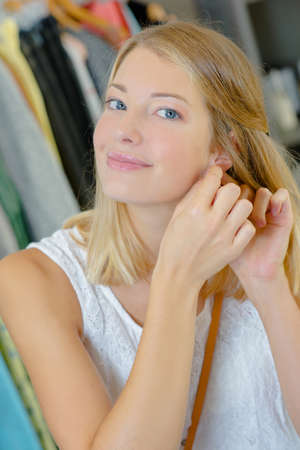 try: Woman trying on a pair of earrings