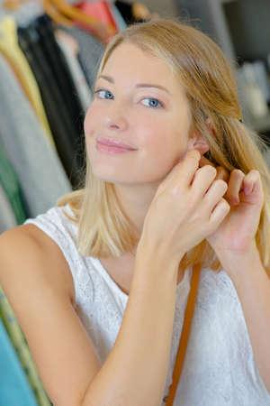 pierced ears: Woman trying on a pair of earrings