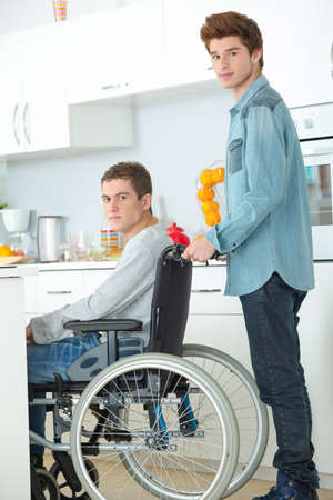 paralyze: Teenager in wheelchair and his friend Stock Photo