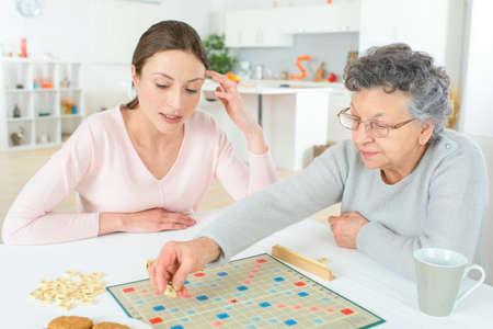 jeu: Une femme �g�e de jouer un jeu de plateau Banque d'images