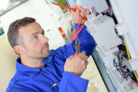 energy electrician: Working on a circuit breaker Stock Photo
