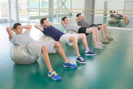 hombres haciendo ejercicio: Cuatro hombres ejercitan en bolas de aer�bicos Foto de archivo