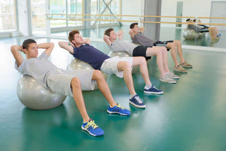 oven range: Four men exercising on aerobic balls