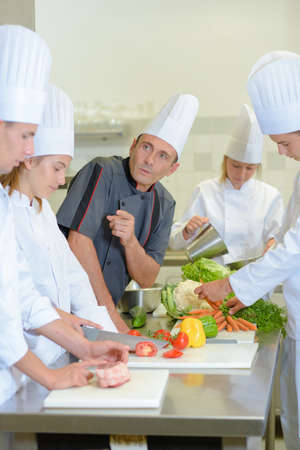 caterers: Chef instructing trainee caterers Stock Photo
