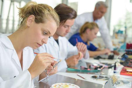 false: Female technician adding colour to false tooth