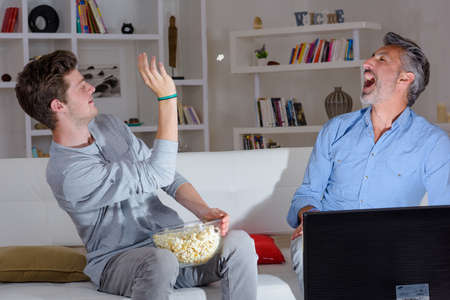 weekend activities: Son throwing popcorn in to fathers mouth Stock Photo