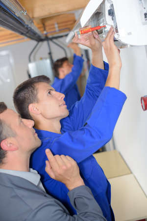instructing: Tutor instructing trainee electrician