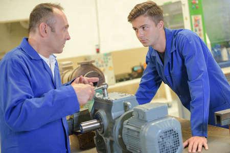 compresor: Man using wrench on machine, apprentice watching