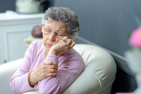 weary: elderly woman on a couch Stock Photo