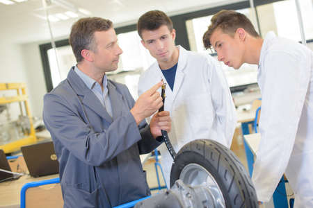 practical: Teacher showing students the adapter for inflating tyre
