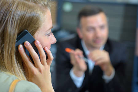lady on phone: Lady on mobile phone, suited man blurred in background Stock Photo