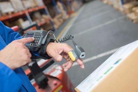 handheld computer: Man in warehouse wearing handheld scanner and computer