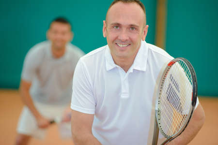 two men: Two smiling men playing tennis