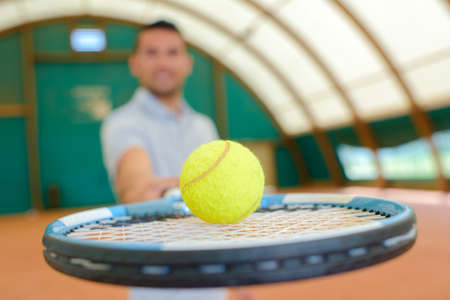 sportsmanship: man holding a tennis racket with a ball Stock Photo