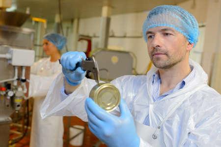tin can: worker measuring tin