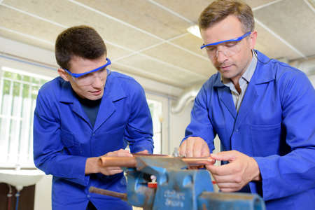 trades: Two engineers working on copper tube held in a vice Stock Photo