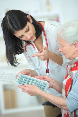 pill box: Nurse helping an old woman with her pill box Stock Photo